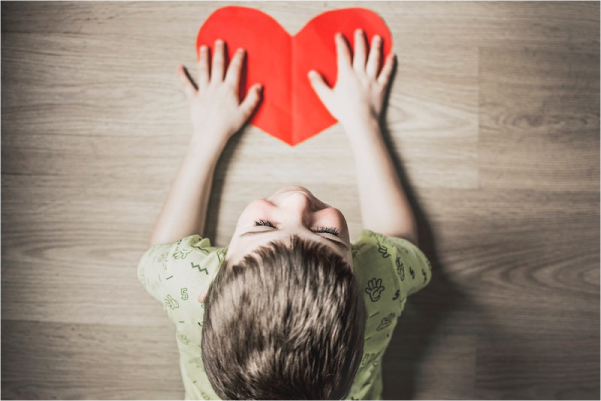 child holding a paper heart